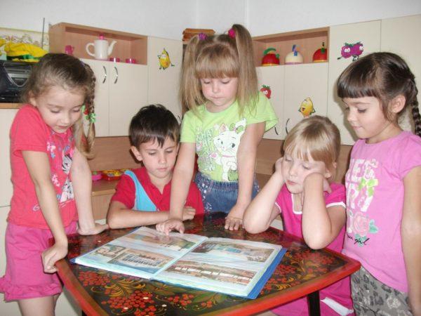 Четыре девочки и мальчик рассматривают иллюстрации в книге
