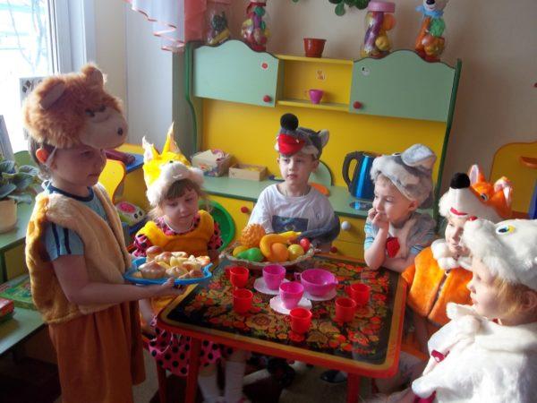 Дети в костюмах животных сидят за столом с игрушечной посудой и фруктами