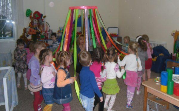 Дети держатся за ленты в игре Карусель