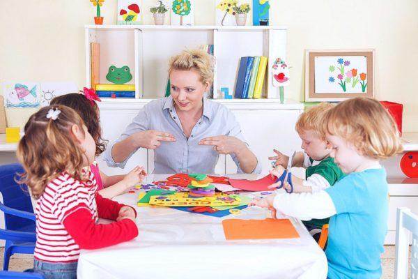 Педагог и дети сидят за столом, у одной девочки ножницы в руках