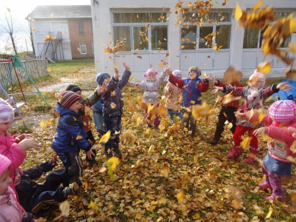 Дети подбрасывают вверх осенние листья на прогулке