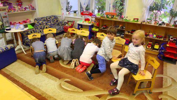 Дети играют, отвернувшись лицом к стульям