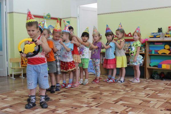 Дети выстроились в шеренгу за мальчиком, держащим в руках игрушечный руль