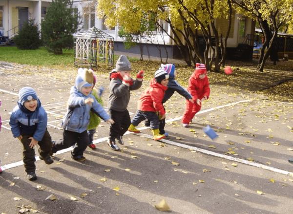 Дети играют в подвижную игру на площадке