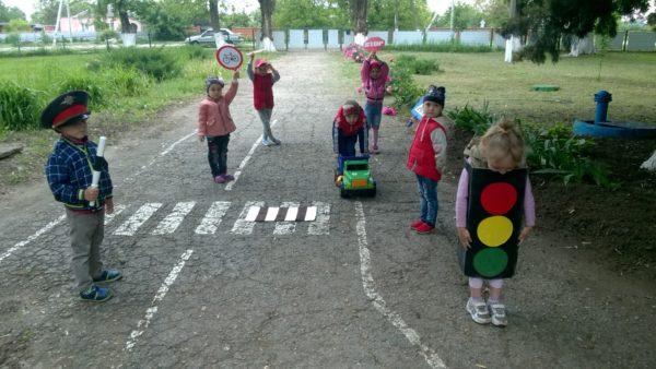 Дети играют в сюжетно-ролевую игру по ПДД на площадке