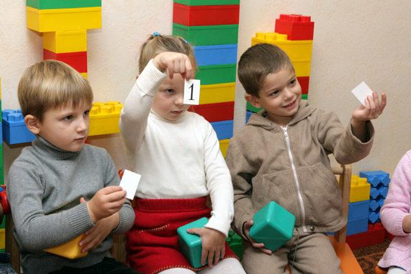 Трое детей держат в руках кубики и карточки с цифрами