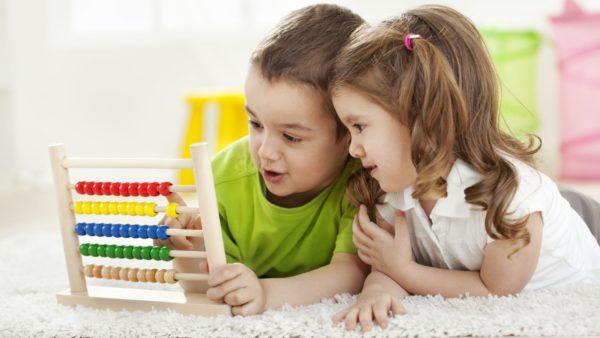 Мальчик и девочка рассматривают счёты