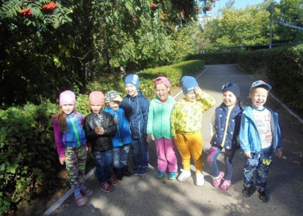 Дети в весенней одежде щурятся на солнце