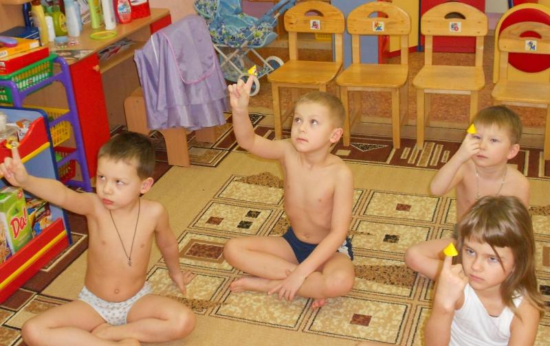 Дети, сидя на ковре, тянут руку вверх