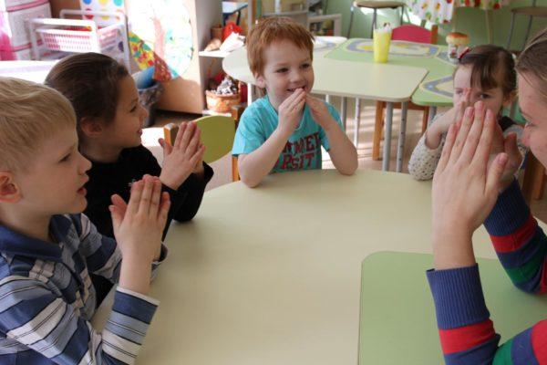 Дети, сидя за столом, показывают домики из сложенных ладошек