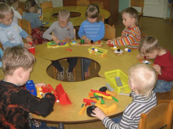 Дети сидят за круглым столом и играют в различные игры