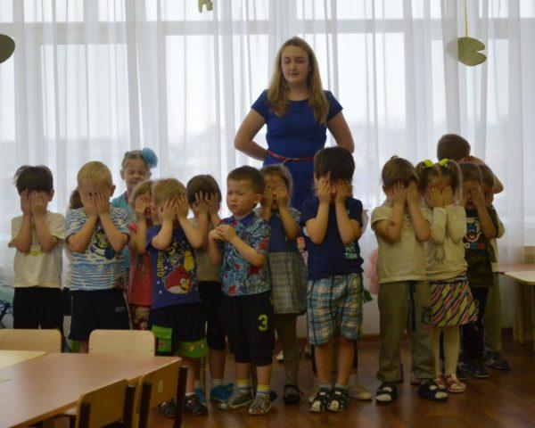 Дети стоят возле воспитательницы, закрыв глаза ладошками