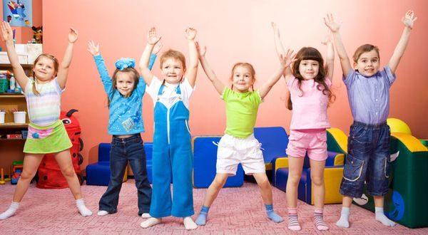 Дети с поднятыми вверх руками веселятся на зарядке