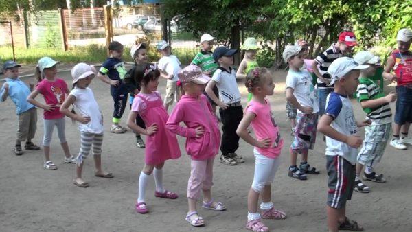 Дети, держа руки на поясе, занимаются зарядкой на территории ДОУ