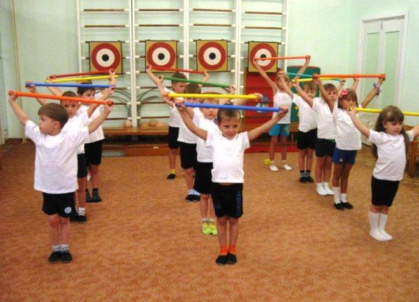 Дети выполняют упражнение с гимнастическими палками
