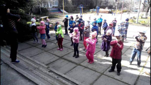 Дети выполняют зарядку на улице