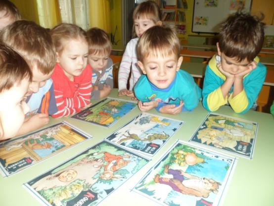 Дети за столом рассматривают иллюстрации