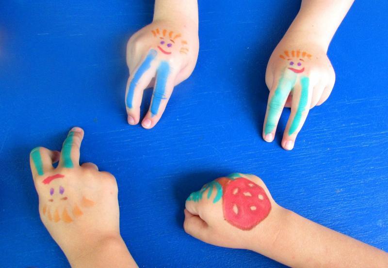Детские руки с нарисованными на них человечками и грибочком