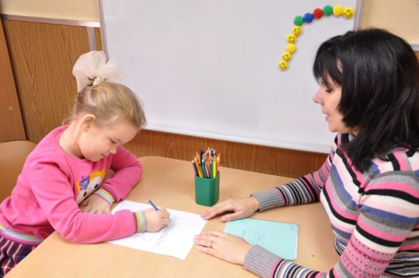 Девочка выполняет задание на листе бумаги, педагог что-то говорит