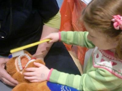Девочка чистит зубы игрушке