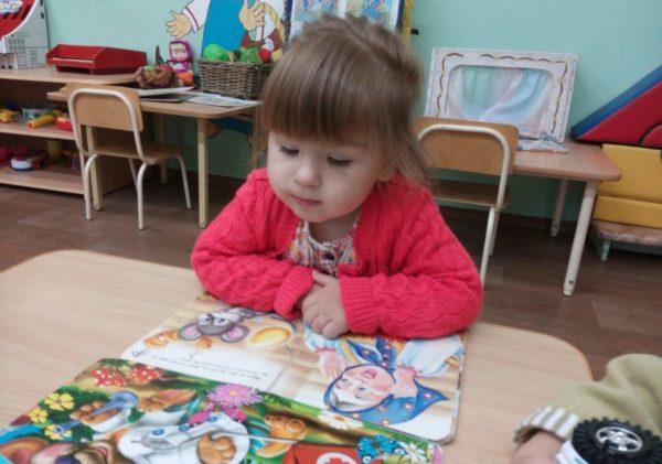 Девочка рассматривает иллюстрации в книге