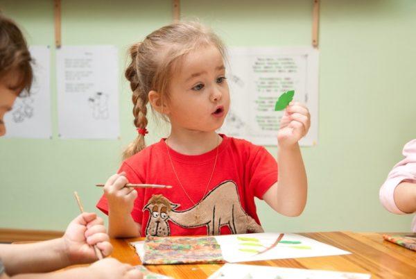 Девочка делает аппликацию из листьев