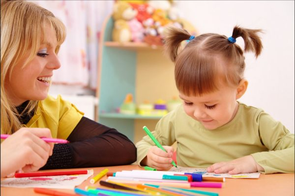 Девочка и педагог рисуют фломастерами