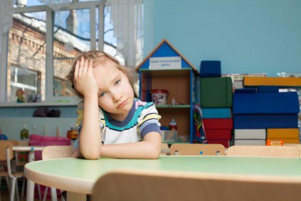 Грустная девочка сидит за столом, взявшись за голову