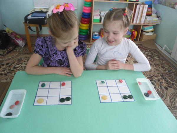 Две девочки выполняют задание, сидя за столом