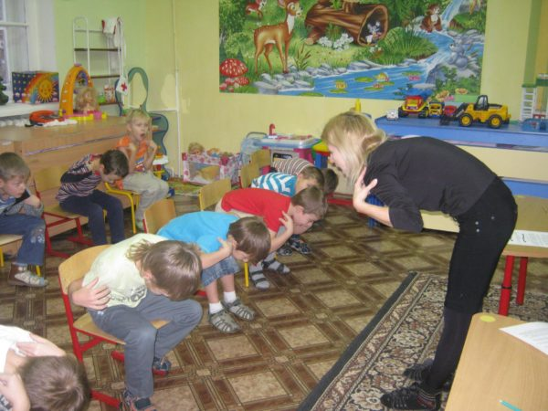 Дети делают физкультминутку на стульчиках, педагог показывает движения