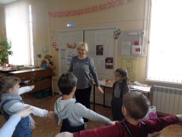 Дети и педагог выполняют упражнение с разведёнными в стороны руками