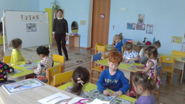 Дошкольники выполняют задание, сидя за партами, педагог стоит у доски с изображениями цифр