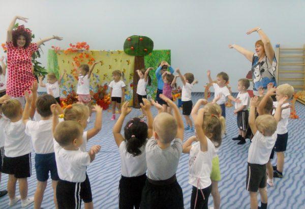 Дети в спортивной форме и два педагога делают зарядку, стоя в кругу