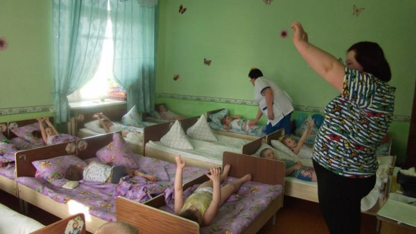Дети выполняют гимнастику в кроватях, педагог показывает движения