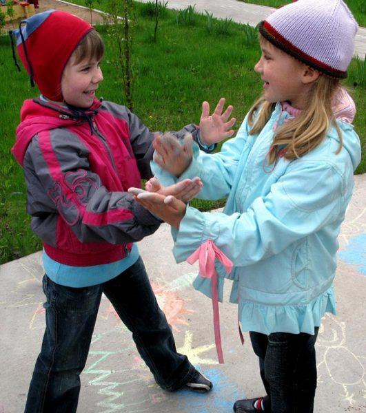 Две девочки играют в игру «Летел лебедь»