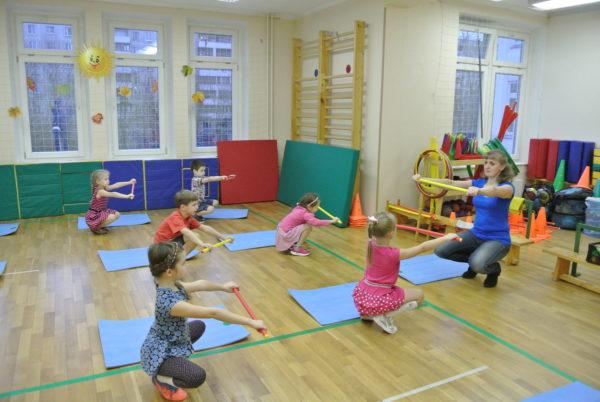 Дети и педагог выполняют приседания с гимнастическими палками в руках