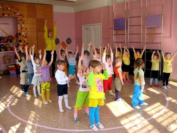 Педагог и группа детей подняли руки вверх