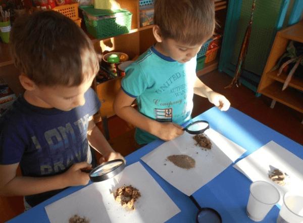 Мальчики изучают состав песка при помощи увеличительных стёкол