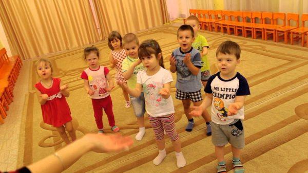 Малыши делают движения руками, подражая педагогу
