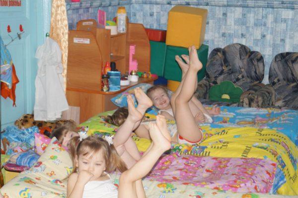 Дети лежат в кроватях, подняв вверх ноги