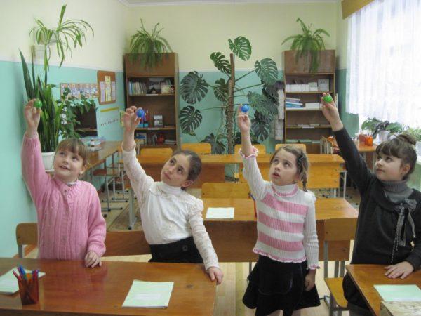 Четыре девочки делают зрительную гимнастику с шариками в руках