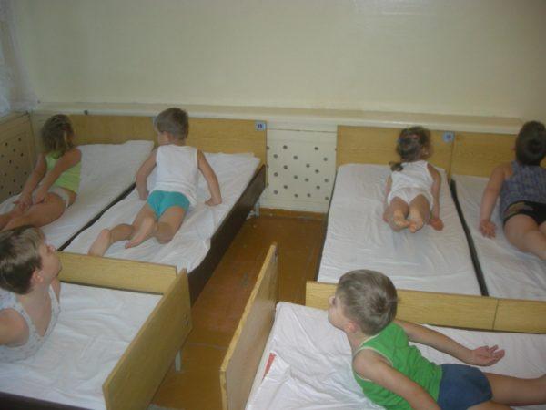 Дети выполняют упражнение, лёжа в кроватках