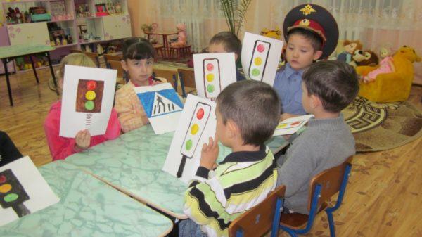 Дети держат в руках рисунки светофоров и дорожного знака