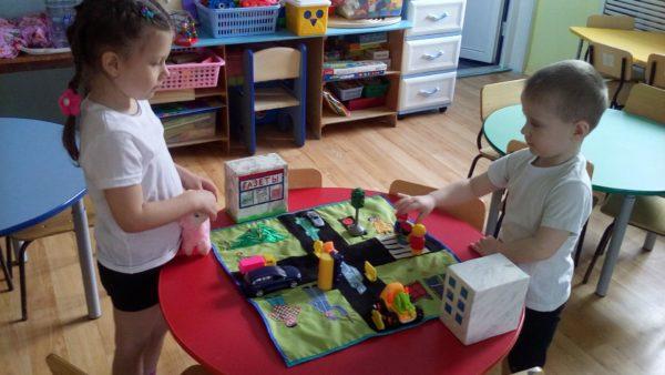 Мальчик и девочка играют с макетом проезжей части
