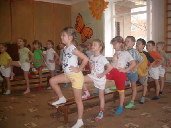 Дети стоят в двух шеренгах, поставив одну ногу на лавочку