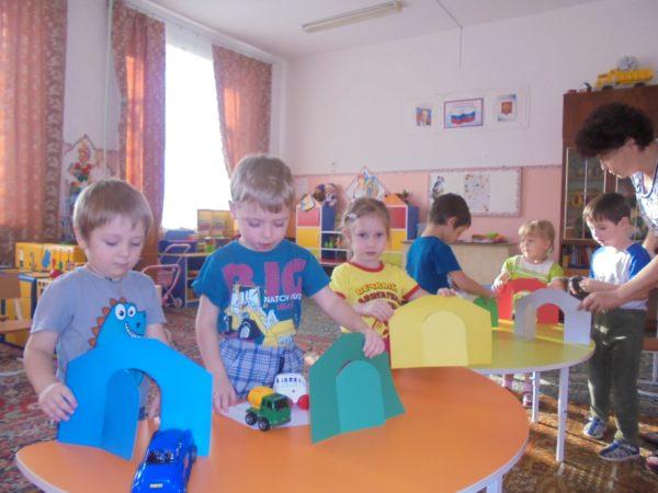 Дети играют с картонными воротами и машинками