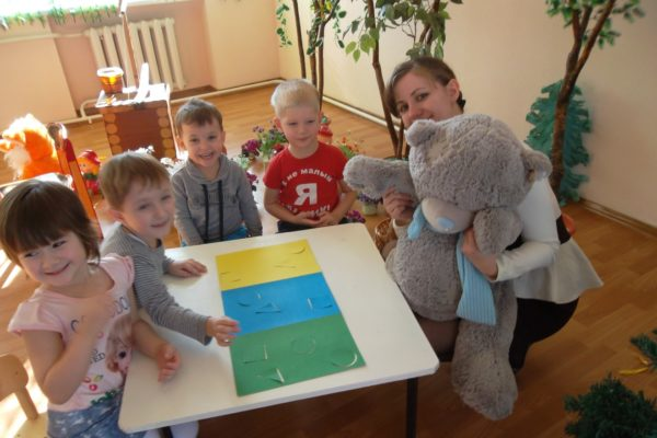 Педагог держит большого плюшевого мишку, дети улыбаются