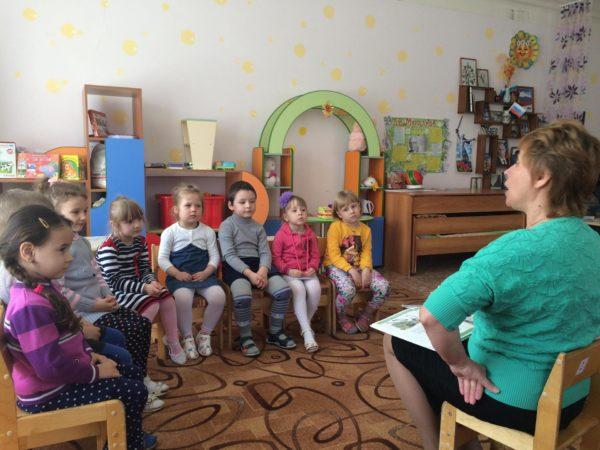 Педагог с книгой на коленях обращается к дошкольникам