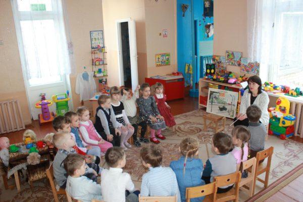 Педагог что-то объясняет детям, сидящим в кругу