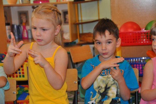 Мальчик и девочка выполняют пальчиковое упражнение